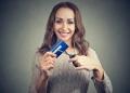 Mujer joven alegre cortando tarjetas de crédito.