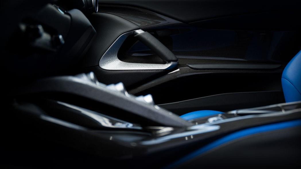 Su interior tiene asientos eléctrico de color azul compuestos de cuero y tela Jeans Ande con arneses de carrera de 4 puntos.