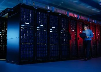 Centro de datos, especialista en TI camina por la fila de racks de servidores con una computadora portátil. Telecomunicaciones, computación en la nube, inteligencia artificial, supercomputadora.