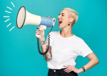 Mujer joven gritando a través de un megáfono sobre un fondo turquesa