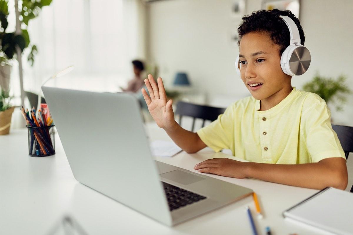 Chico latino y negro haciendo videollamadas e-learning a través de una computadora portátil.