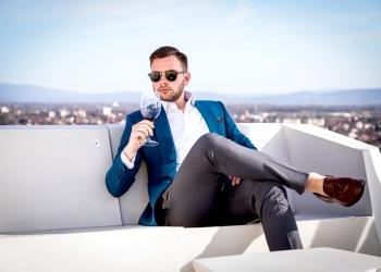 Hombre millonario con un caro traje hecho a medida, sentado al aire libre con gafas y sosteniendo una copa de vino tinto