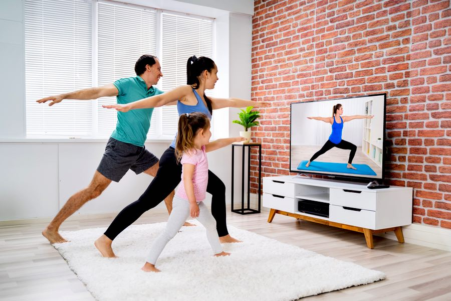 Familia haciendo ejercicio físico en casa.