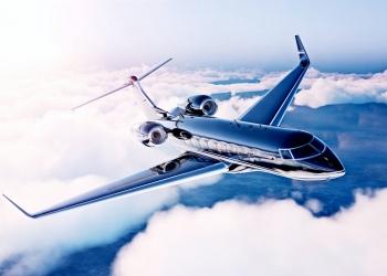 Jet privado de lujo negro volando en el cielo azul al amanecer.
