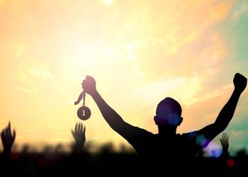 silueta de una mano sosteniendo la medalla de oro en un estadio deportivo