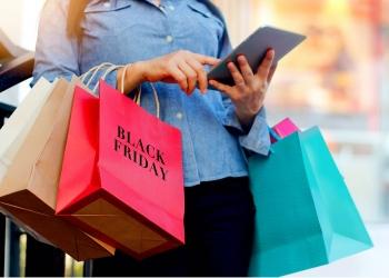 Mujer usa tableta y sostiene el bolso de compras de Black Friday.