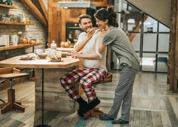 Pareja en pijama desayunando en la cocina.