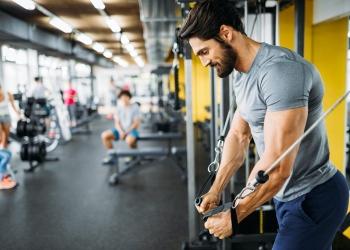 fisicoculturista muscular que hace ejercicios en el gimnasio