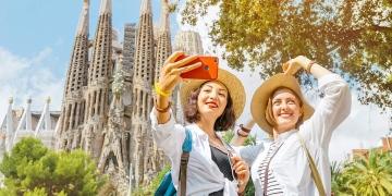 Mujeres tomando fotos selfie en su teléfono inteligente frente a la catedral católica de la Sagrada Familia en Barcelona, España.