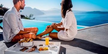 Pareja desayuna junto a una piscina infinita con vistas al océano Caldera de Santorini, Grecia.