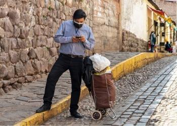 Empresario con máscara y teléfono móvil durante la pandemia de coronavirus covid-19 en Cusco, Perú en América del Sur.