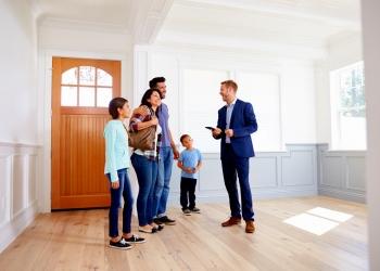 Agente inmobiliario mostrando alrededor de casa nueva a una familia.