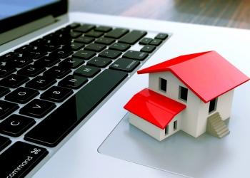 Pequeña casa encima del teclado de una computadora. Agencia inmobiliaria online.