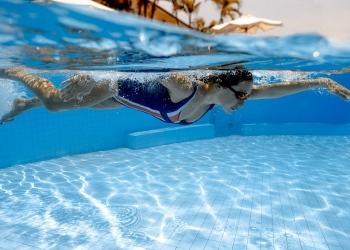 Nadadora, saltando y zambulléndose en la piscina.
