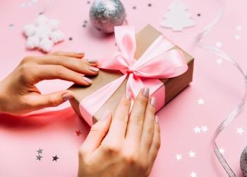 Manos femeninas con manicura de moda con caja de regalo sobre fondo festivo de Navidad.