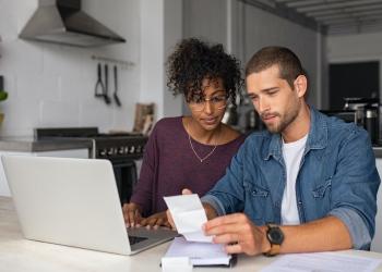 Joven pareja multiétnica examinando las finanzas del hogar