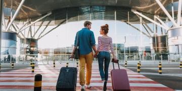 Pareja caminando y llevando sus maletas trolley al aeropuerto.