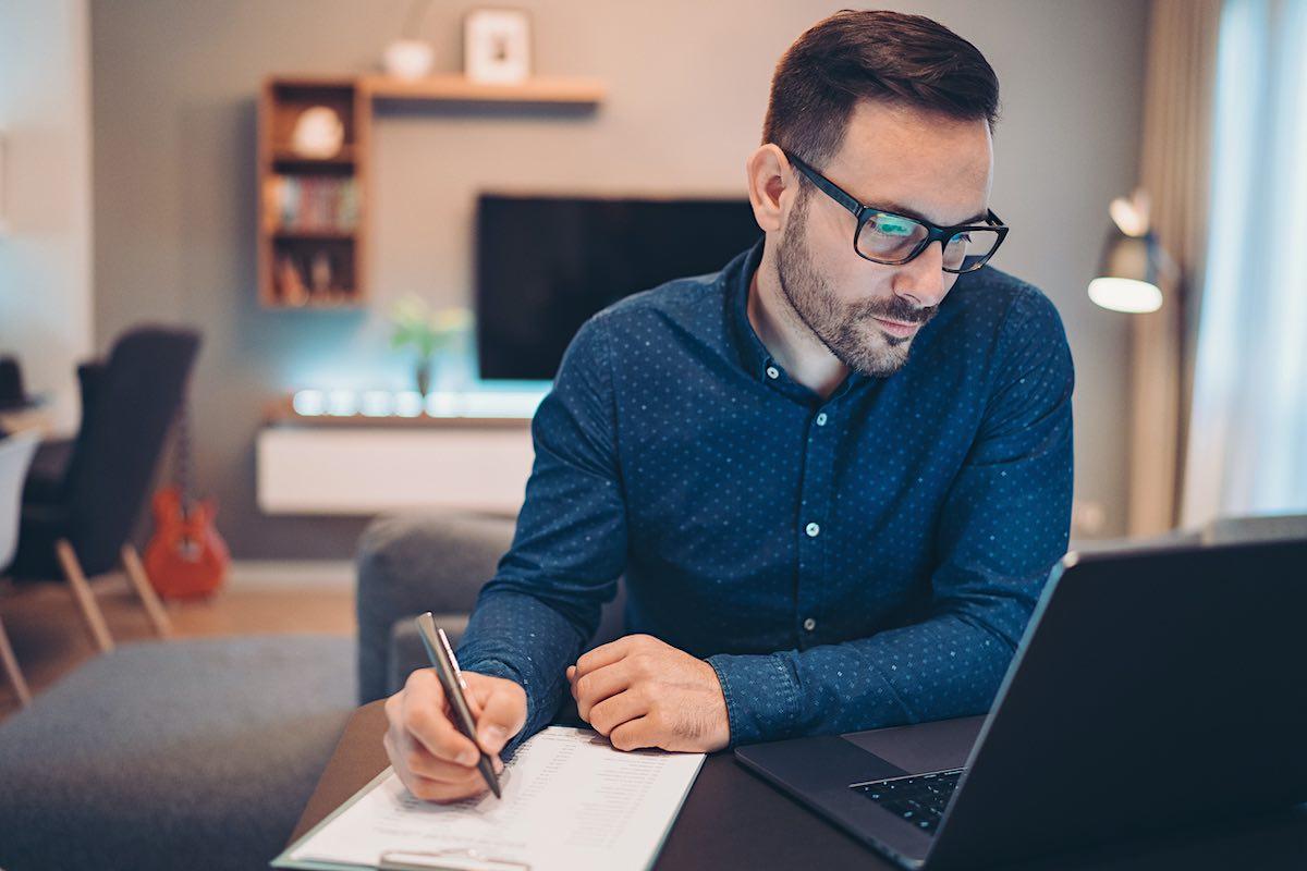 Empresario usando laptop y haciendo trámites en casa.