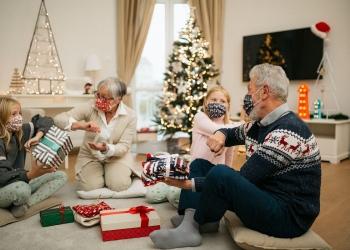 Familia disfrutando fiestas navideñas en casa, saludos de codo por Covid-19.