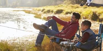 Padre e hijo en un viaje de pesca y acampando junto a un lago.