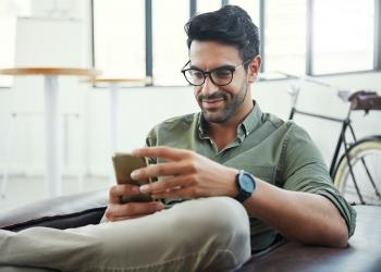 Hombre sentado en el sofá con su teléfono inteligente.