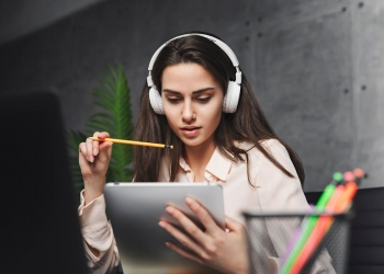 Chica en auriculares aprendiendo idiomas en línea. Escuchando música y trabajando en un proyecto. auriculares inalámbricos. Estudiante.