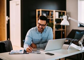 Hombre de negocios trabajando en casa con laptop y papeles en el escritorio