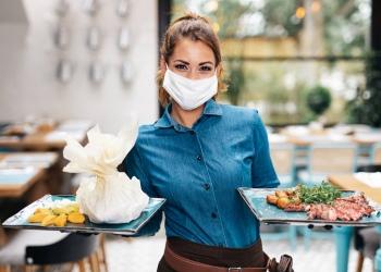 Joven camarera con máscara protectora facial trabajando en restaurante exclusivo.