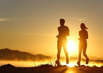 pareja corriendo al atardecer con el sol de fondo.