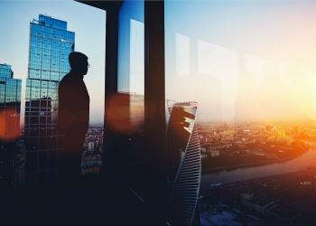Hombre descansando después de una reunión de negocios mirando la ciudad.