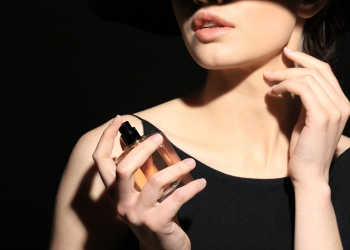 Mujer joven con botella de perfume sobre fondo oscuro