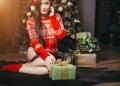 Mujer en bragas elegantes y suéter con regalos delante del árbol de Navidad.