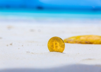Moneda de Bitcoin en la playa.