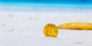 Moneda de Bitcoin en la playa.