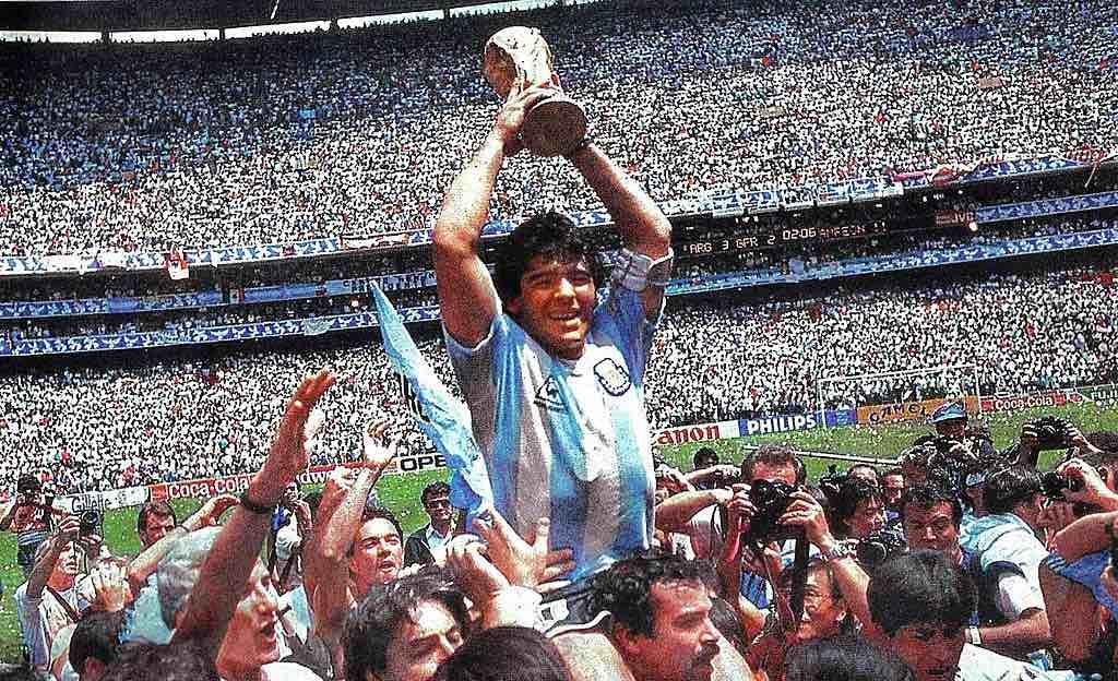 El El Pibe de Oro dando la vuelta olímpica en el Estadio Azteca con la Copa del Mundo en sus manos.