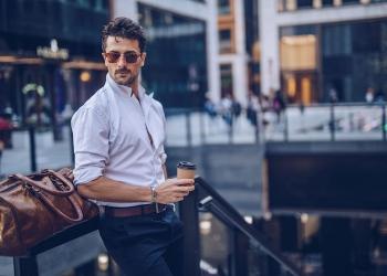 Hombre empresario elegante con café y un maletín de viaje.