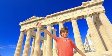 Niño feliz tomando una fotografía delante del Partenón de Atenas, Grecia.