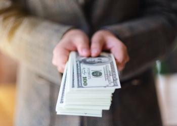 Mujer sosteniendo billetes de dólar americano en efectivo. financiamiento.