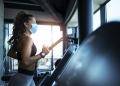 Mujer corriendo en una cinta en el gimnasio y usando mascarilla contra el coronavirus covid-19.