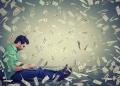 Hombre usando una computadora portátil para su negocio en línea con dinero en efectivo en dólares lloviendo.