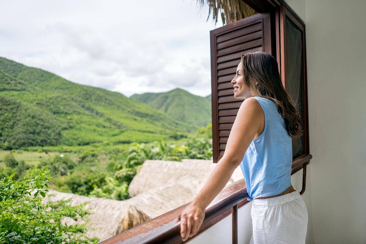 Mujer viajando y disfrutando de la vista desde su habitación de hotel