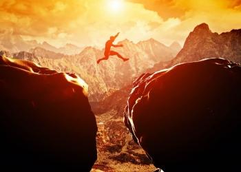 Hombre saltando por un precipicio entre dos montañas rocosas al atardecer. Libertad, riesgo, desafío, éxito.