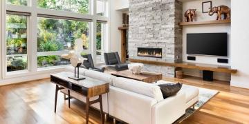 Sala de estar con pisos de madera noble y chimenea en una casa de lujo.