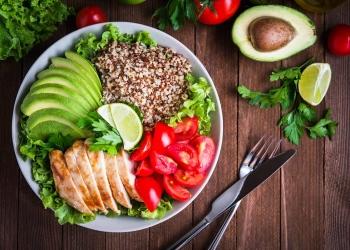 Ensalada saludable con quinoa, tomates, pollo, aguacate y verduras mixtas. Comida y salud.