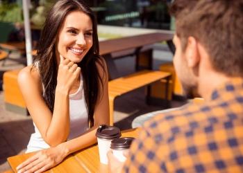 Pareja de enamorados hablando fuera de la cafetería y tomando café.