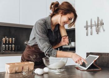Mujer joven en la cocina y cocinando. Mirando la tableta.