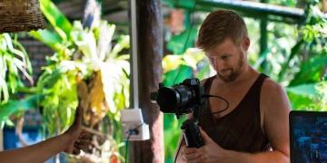 Operador de cámara de video profesional filmando a un influencer Youtuber.