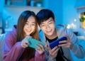Pareja asiática juegando en teléfono inteligente juego para móviles.