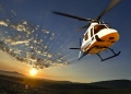 Helicóptero modelo Augusta volando sobre viñedos iluminados por el sol de la tarde.