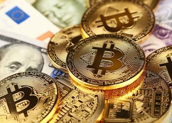 Monedas de bitcoin de oro sobre billetes de euro, dólar, libra y yuan